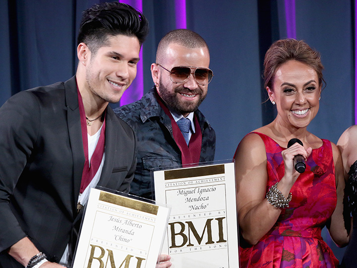 Honorees Chino & Nacho accept award from BMI Vice President, Writer/Publisher Relations, Latin Music Delia Orjuela onstage