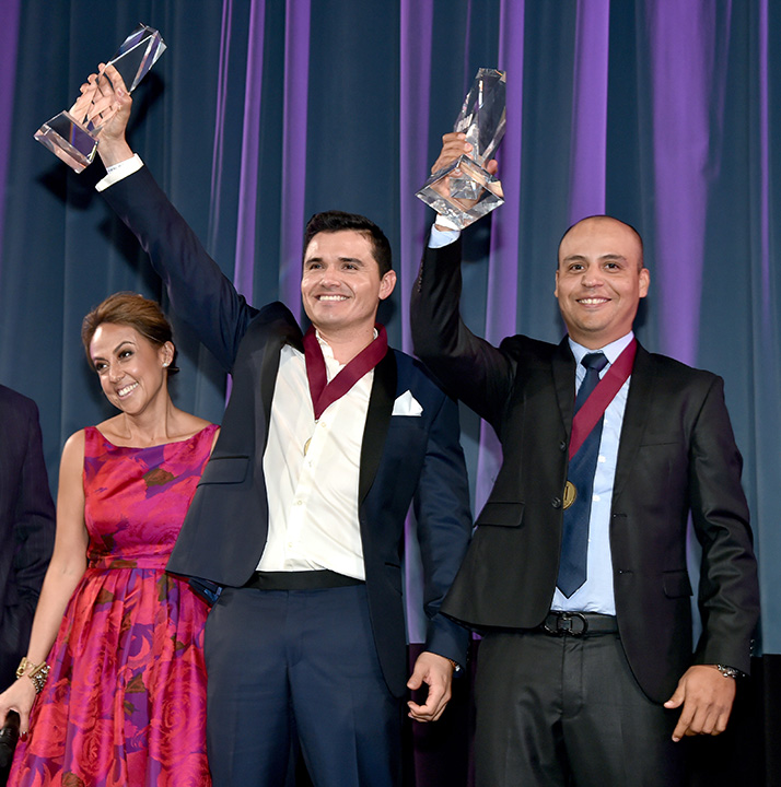 BMI Vice President, Writer/Publisher Relations, Latin Music Delia Orjuela with honorees Horacio Palencia and Jesus Omar Tarazon accepting awards onstage